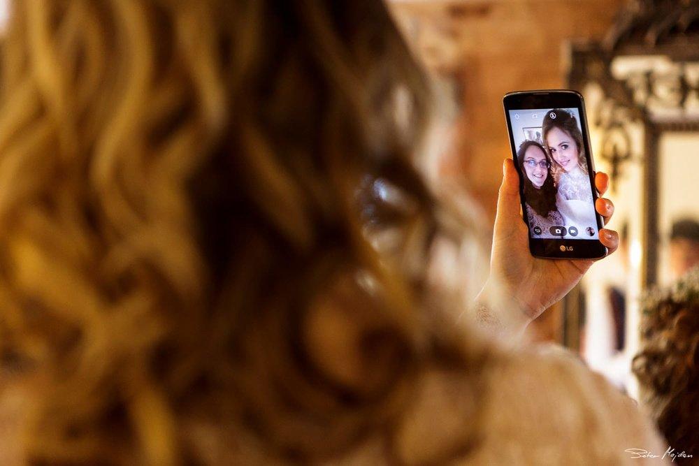 bride taking selfie with bridesmaid