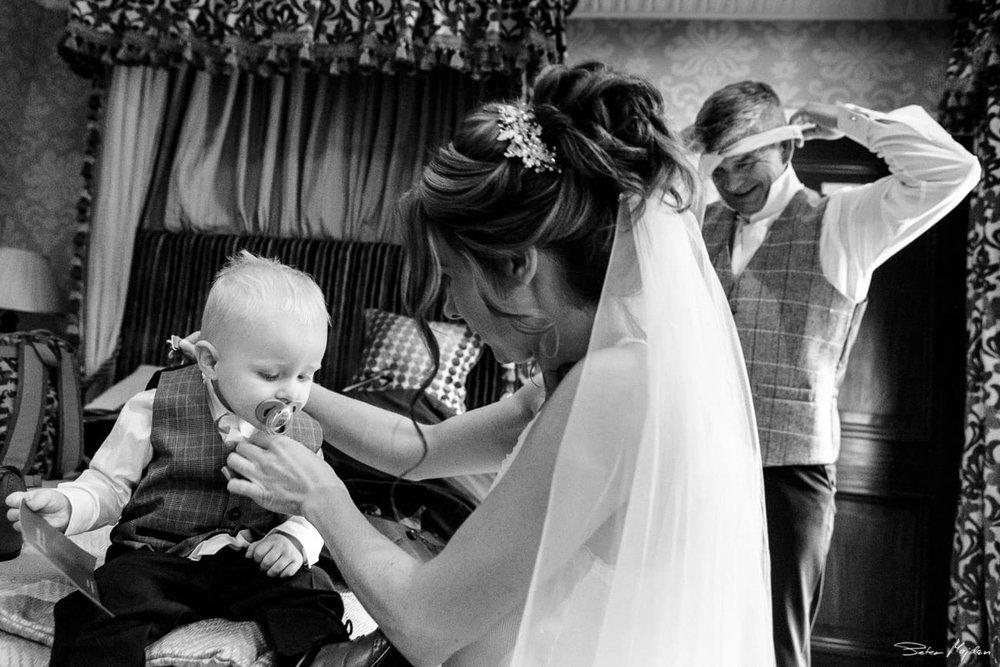 bride dressing her little son