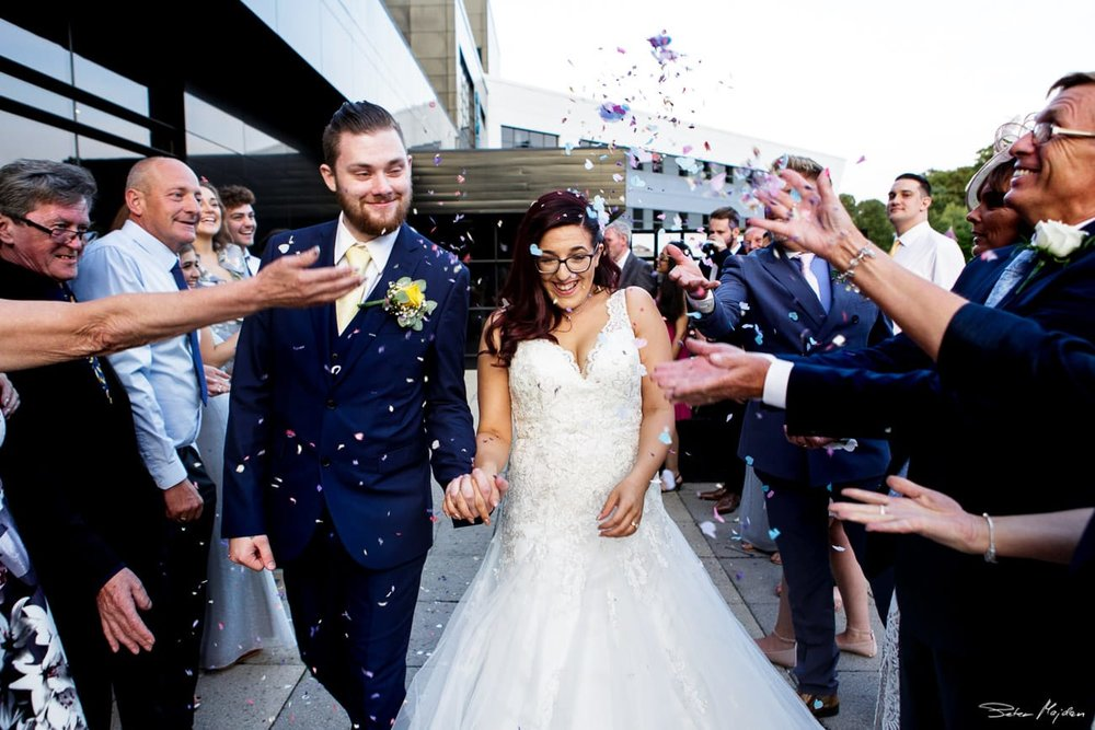 guests throwing confetti at newlywed