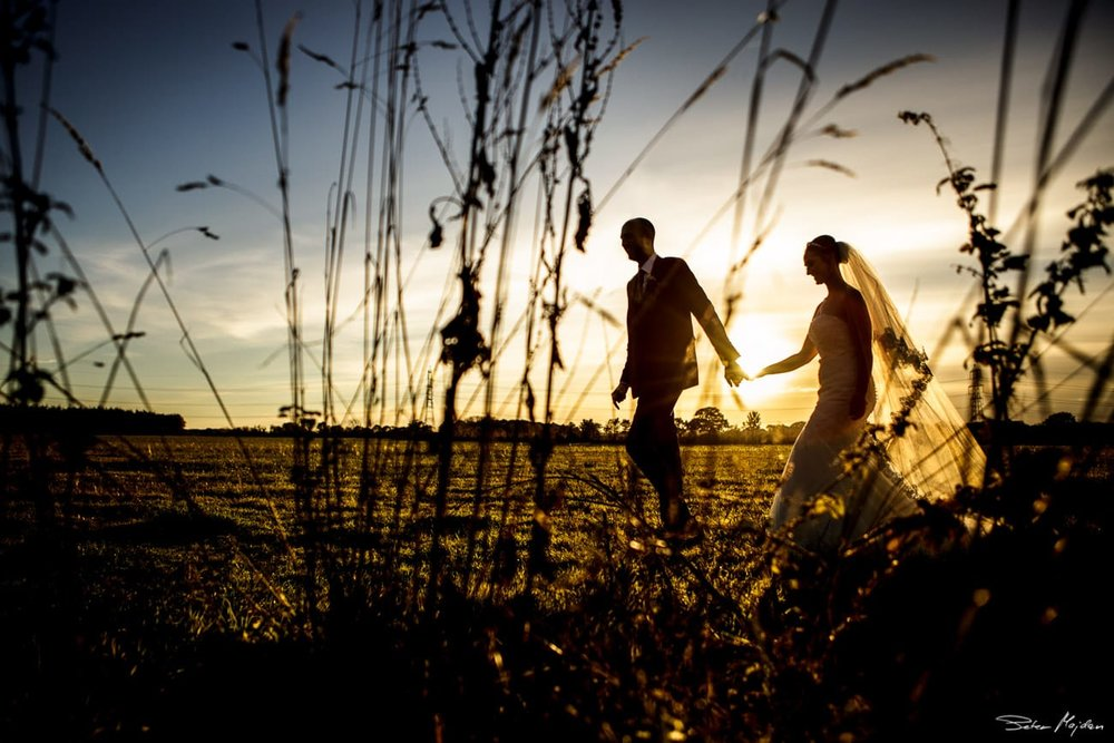 bride and groom walking through fields at sunset