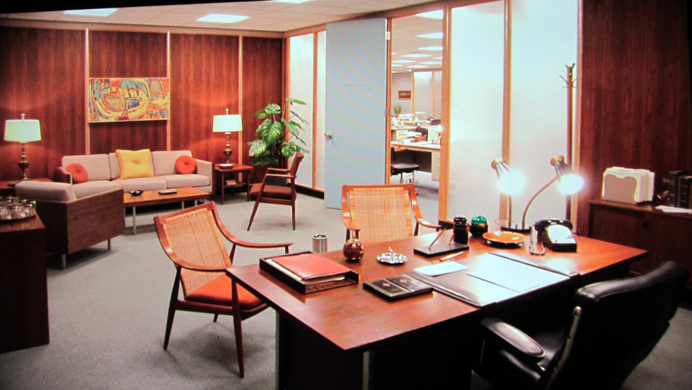 Don Draper's office featuring the Eames Time-Life Executive chair, two Hvidt/Mølgaard-Nielsen FD-146 chairs and a twin 1950's table lamp.