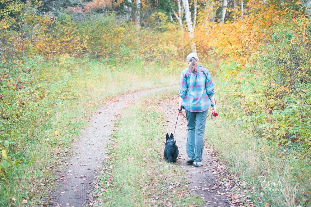 Woman walking her Scottish Terrier at Kakabeka Falls Provincial Park in autumn
