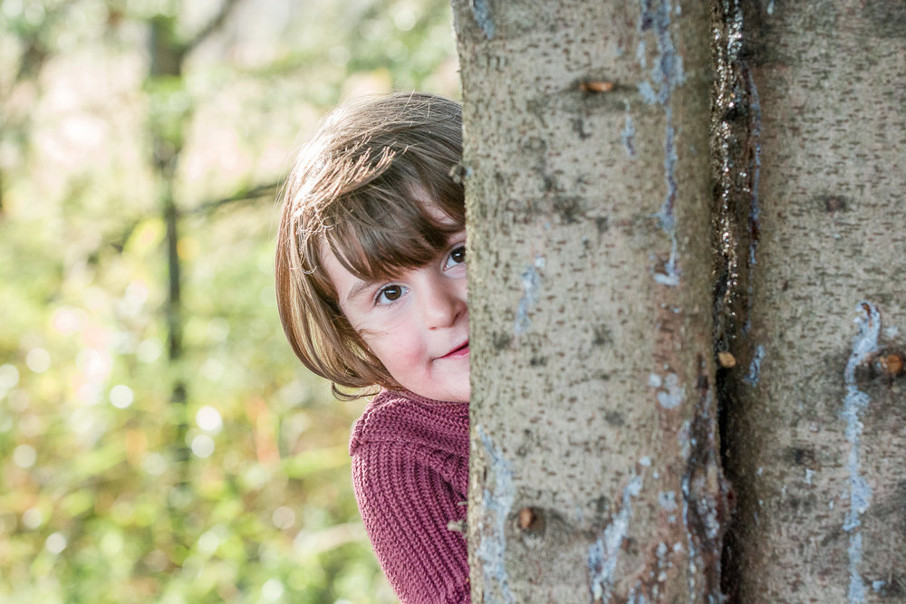 girl peering around a tree