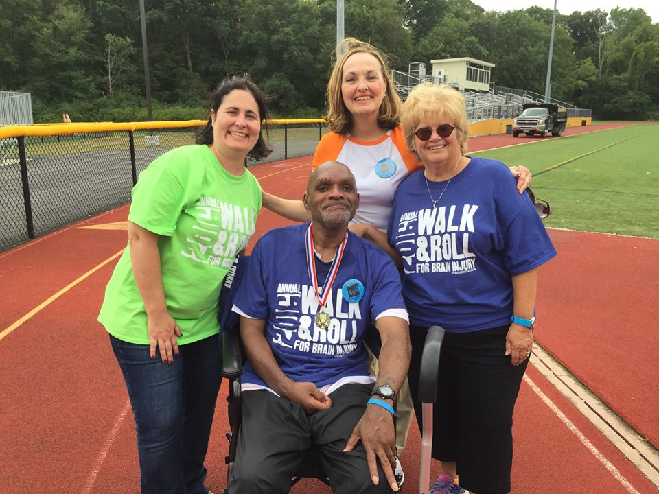 CRC staff congratulate a client for finishing a lap of the track at the Brain Injury Association of Massachusetts Walk & Roll