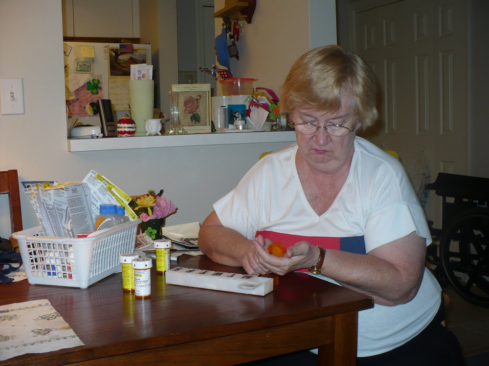 A client recovering from acquired brain injury practices filling her pill box during an outpatient occupational therapy session