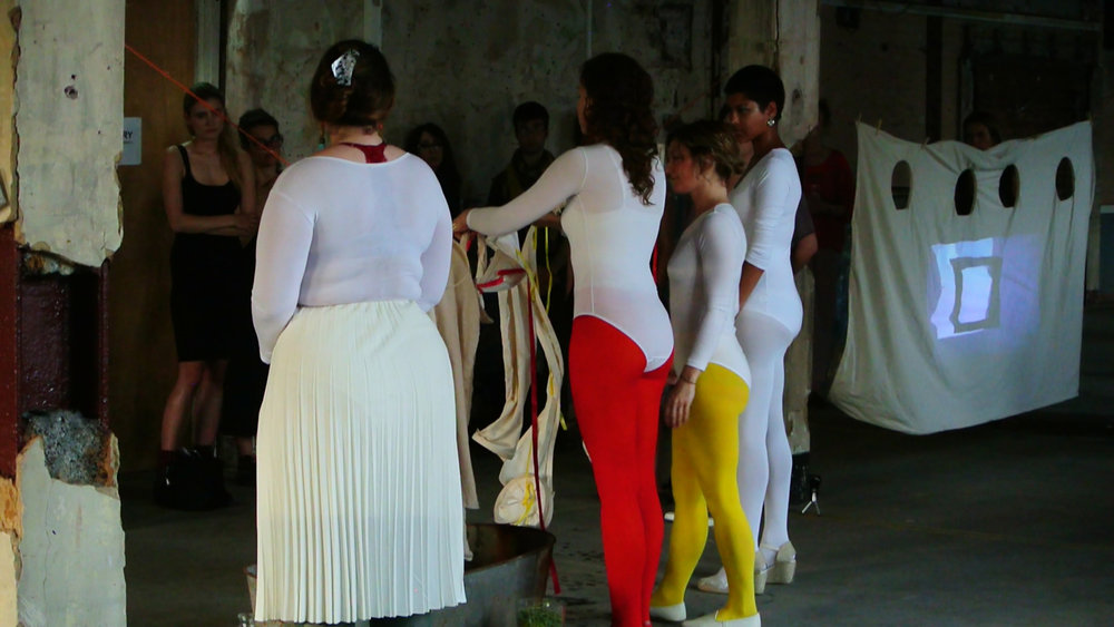 """Still from Performance of """"Emilia Galotti's Colouring Book of Feelings,"""" written by Sophie Seita at the Bargehouse/ Oxo Tower Wharf for Art Night 2018 in London. Installation featuring video by Simone Kearney and Lanny Jordan Jackson. Audio work by Rhodri Karim. Sculptural garments by Ciara Philips and Kat Addis. Performers: Sophie Seita, Kat Addis, Nisha Ramayya, Jocelyn Spaar Erin Robinsong, Emma Stirling. Producer: Liv Carr-Archer."""