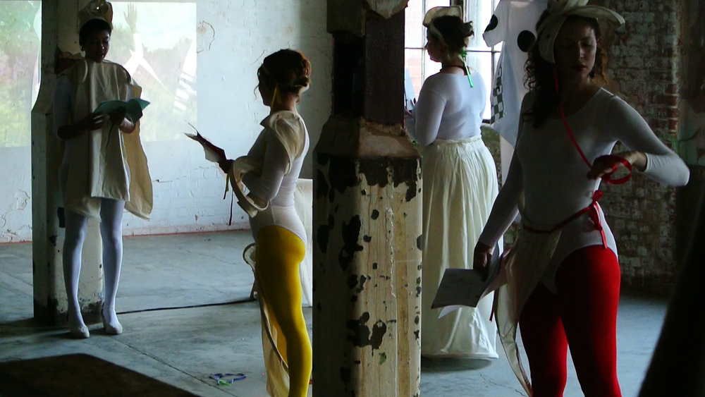 "Still from Performance of ""Emilia Galotti's Colouring Book of Feelings,"" written by Sophie Seita at the Bargehouse/ Oxo Tower Wharf for Art Night 2018 in London. Installation featuring video by Simone Kearney and Lanny Jordan Jackson. Audio work by Rhodri Karim. Sculptural garments by Ciara Philips and Kat Addis. Performers: Sophie Seita, Kat Addis, Nisha Ramayya, Jocelyn Spaar Erin Robinsong, Emma Stirling. Producer: Liv Carr-Archer."