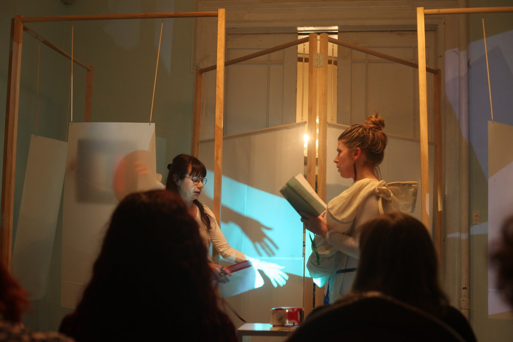 "Still from Performance of ""Emilia Galotti's Colouring Book of Feelings,"" written by Sophie Seita at Torn Page, Chelsea, NY, May 2018. Installation featuring sculptures and video projections by Simone Kearney. Audio work by Rhodri Karim. Sculptural garments by Kat Addis. Performers: Sophie Seita, Jocelyn Spaar, Corina Copp, Bridget Talone."