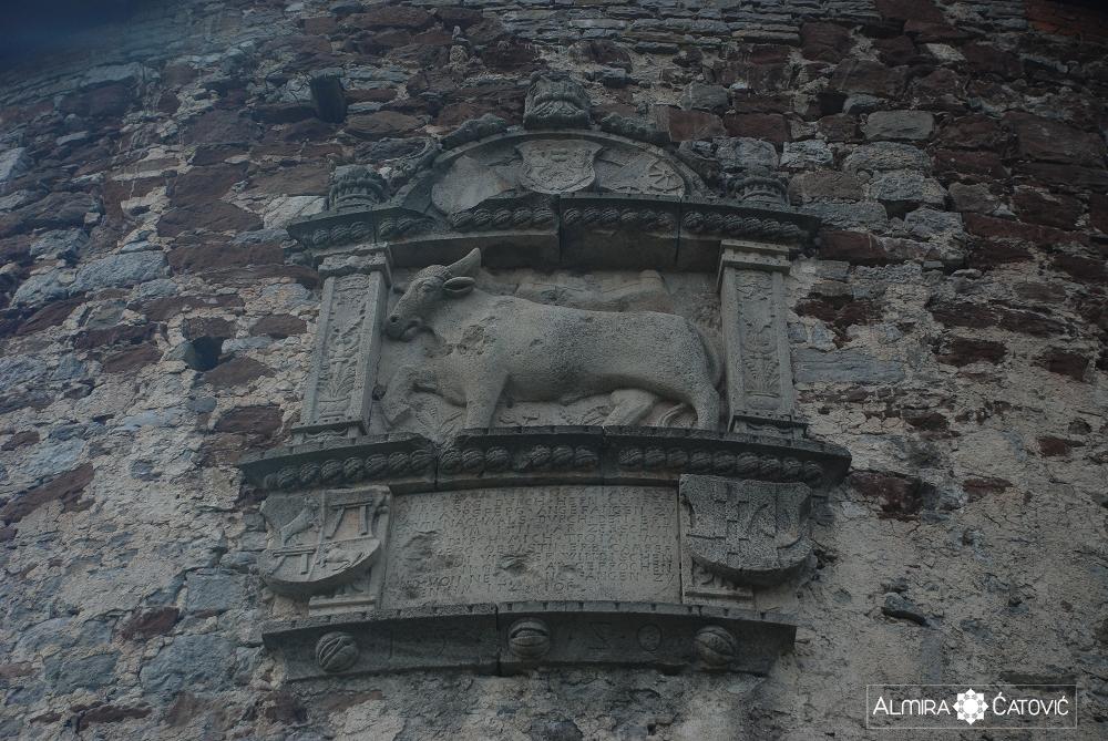 Vklesana podoba tura, grb in besedilo na Volovskem stolpu
