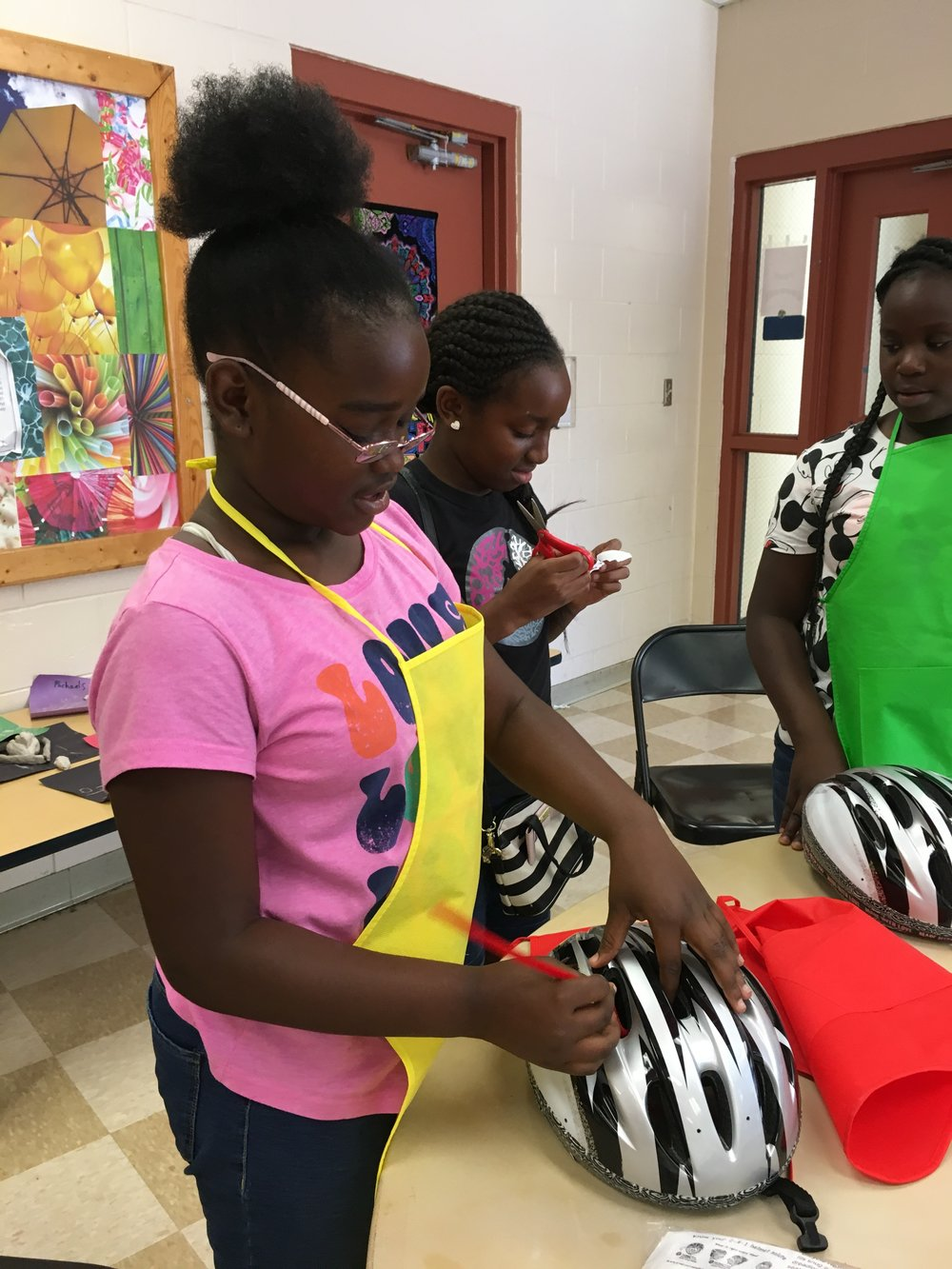 "This student at Thomas ""Jet"" Jackson Rec. Center is tying off her chenille stem through the breather holes in the top of the helmet.  Sometimes the stem extension was curled afterward."