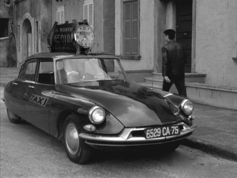 A photograph of a 1960 Citroen DS 19 taxicab on the streets of Paris with the advertisement superimposed on the roof.
