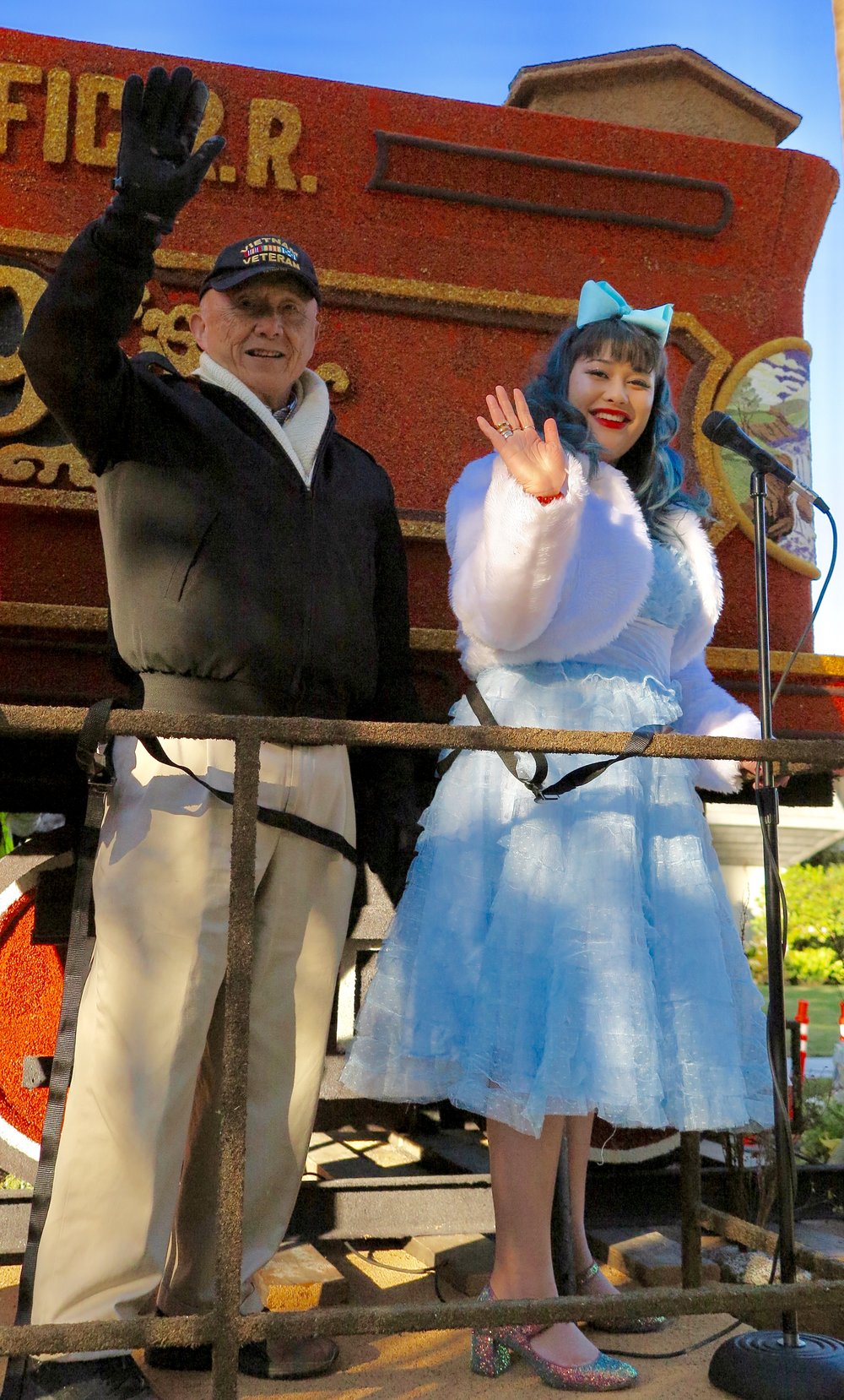 Major General Chen and Blythe Schulte wave as the float begins its journey down the parade route. All riders were safety strapped to the float.