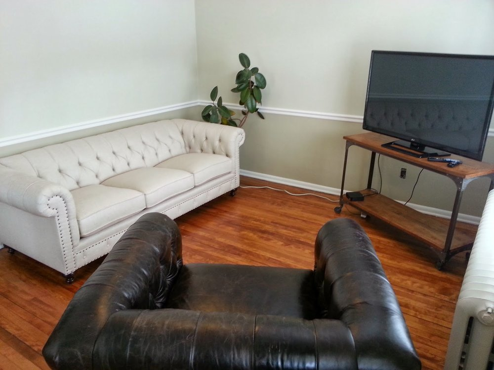 BEFORE: Living room. New homeowner painted the walls. Refinished the hardwood floors. Purchased a sofa, leather chair, TV and then stopped.