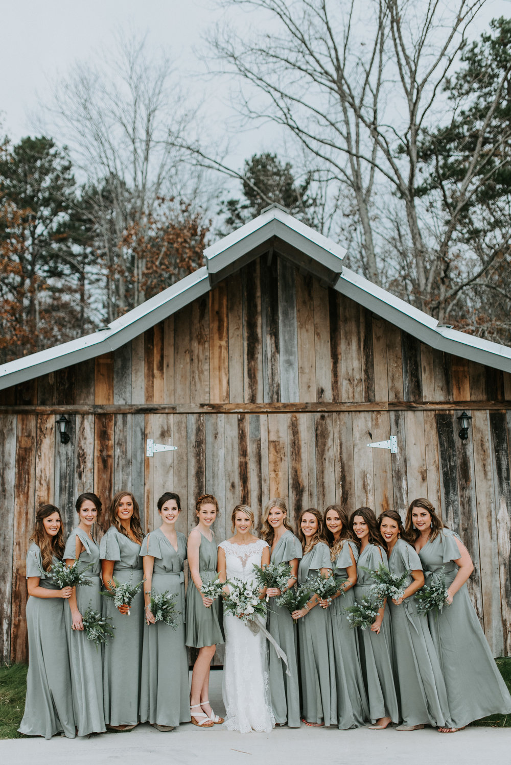 bridesmaids in front of old barn with distressed wood greenery bouquets with ribbons