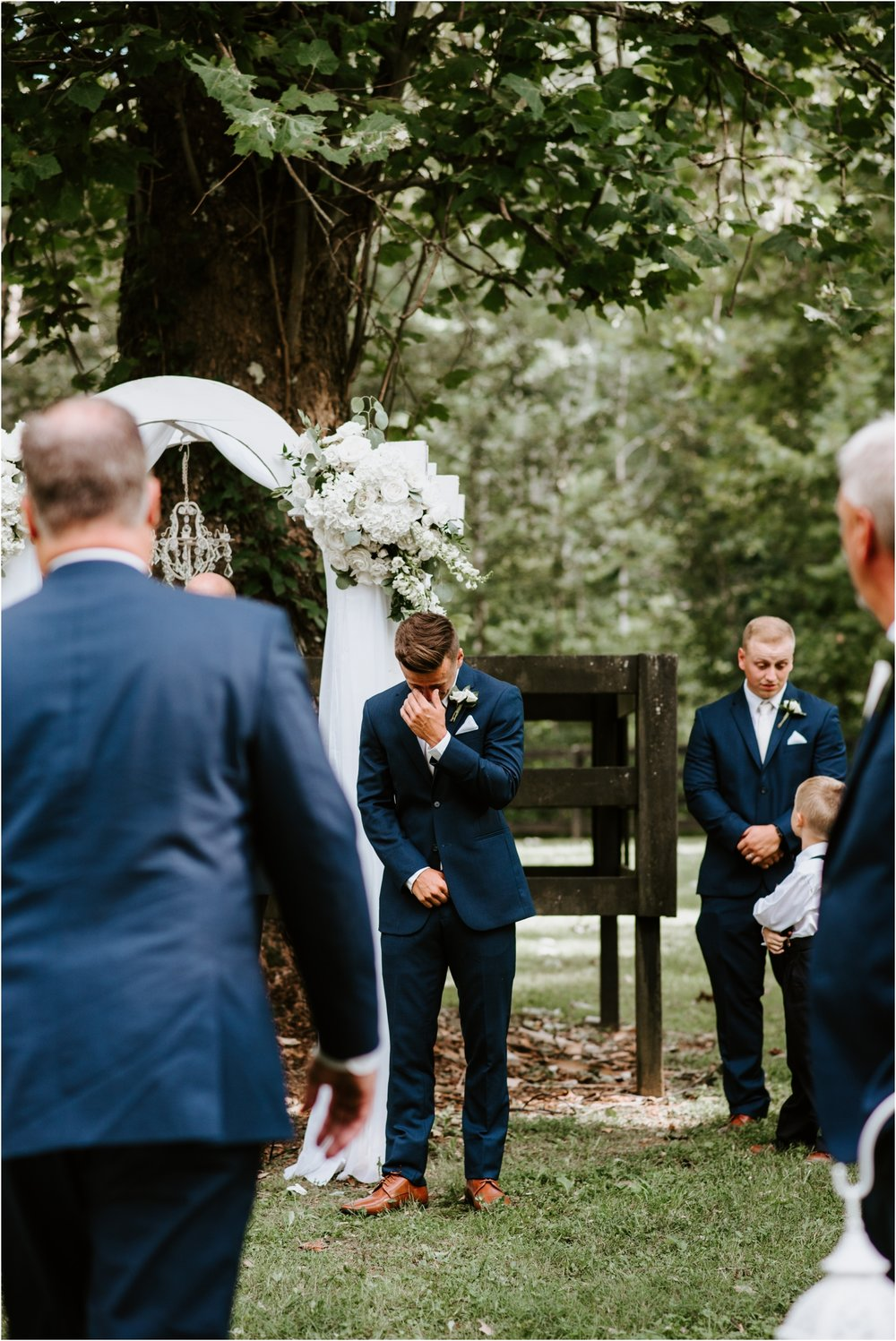 groom crying when bride walks down the aisle navy suit