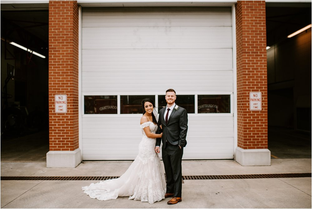 fire station bride and groom portrait in front of white garage door
