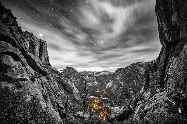 """The Valley of Dreams"" : Yosemite. My first time amongst these guardian cliffs, these Earth giants. I climb with them, into the sky. A waterfall cascades over the cliff's edge, free falling into bliss. Its movement magic, given the snow and ice tracing patches all around me. Thousands of feet it falls. : I rise, as the sun slips ever closer to its nightly kiss, to its dissolving into the beyond abyss. An ever-unfolding sunset comes, as I climb to meet it in each moment, again and again. : I reach the peak, just in time to feel the last moments of sunlights dance, painting in rays the Earth around me. And then it dives. Into the horizon, to gaze upon another world. : Midst snow and ice, I pitch my tent atop Yosemite Point. Yet the night summons me from my sleeping bag's embrace. I retrace miles by moonlight, my descent called to an unmarked spot along the trail's falling back to Earth. I set up my tripod & take only one shot, a long-exposure, 30 seconds. Intuition. : The lights of Yosemite Valley below, I feel them as though the fire of humanity, held by the guardian mountains all around. And their story comes alive, as the long exposure emphasizes the lights as though a fire, shows the dance of clouds across the sky, the journey of a shooting star and satellite. And somehow, in this flash of time, in the middle of a January night, a car glides by in the world below. : It's these tastes of the unimaginable, the magic gifted by the universe, they let me know I'm home. : Link for purchase details & more world travels: http://www.thebarefootprint.com/store/the-valley-of-dreams Clickable link in bio. 💙"