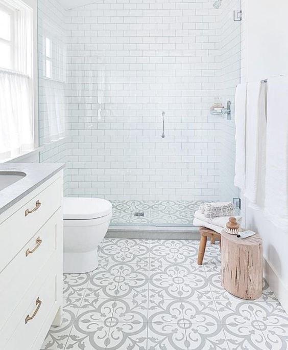 These floral tiles look so fashionable against the clean and modern subway tiles and wooden stools.