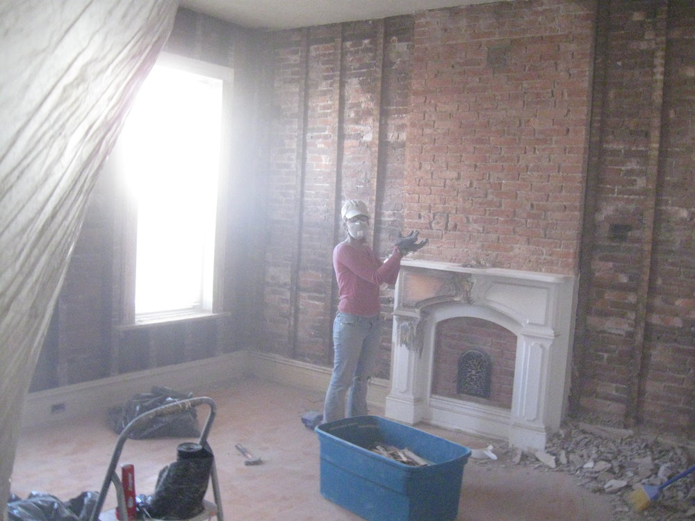 My lovely wife, Athena, showcasing our freshly demolished living room, in 2011.