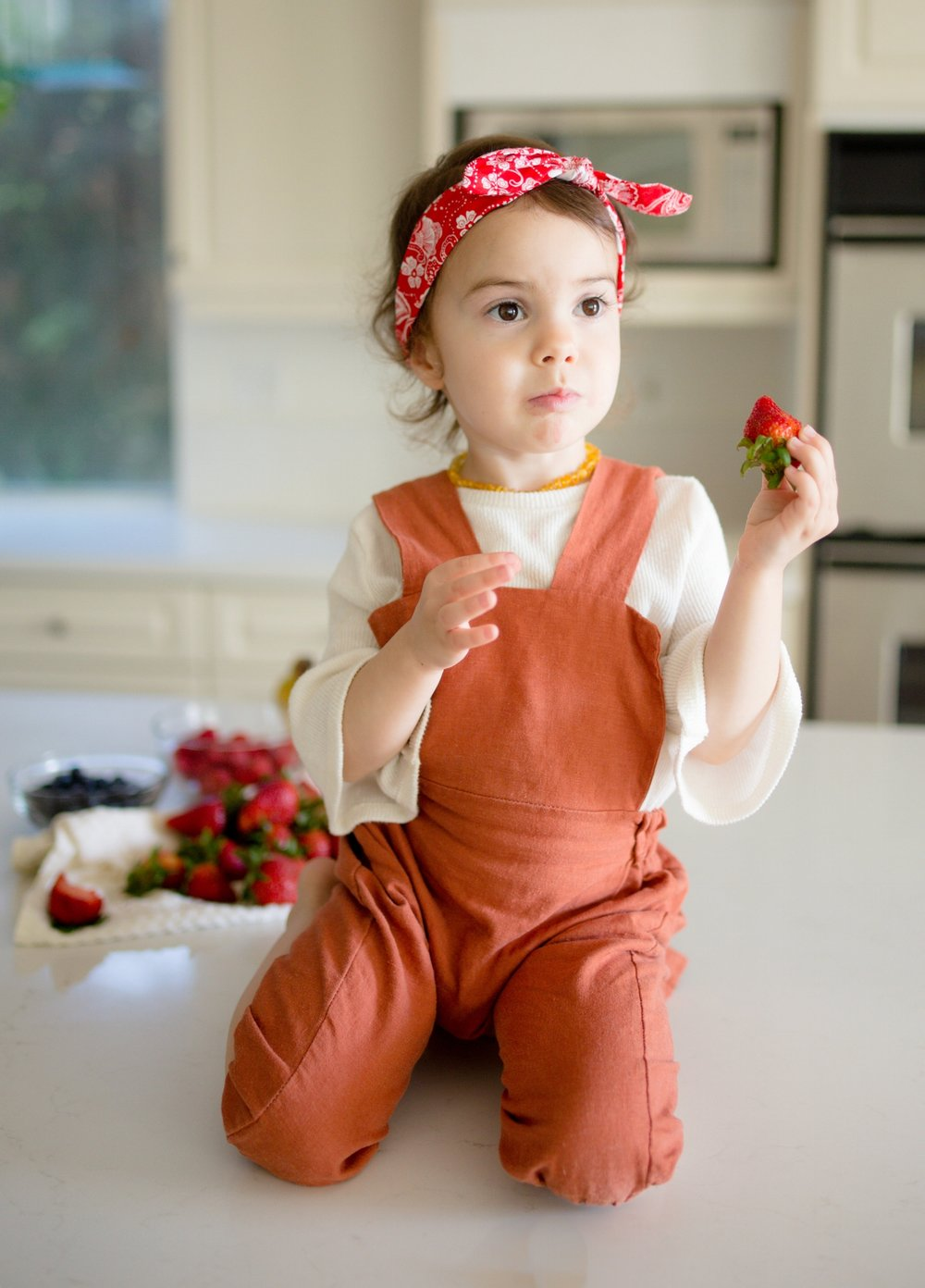 Toddler girl in rust jumpsuit eating fresh strawberries on kitchen counter