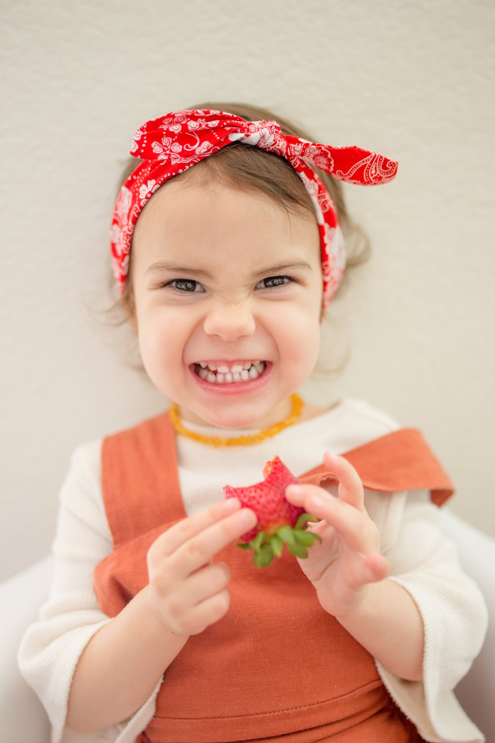 Toddler girl with red bandana eating fresh strawberry with a huge smile on her face