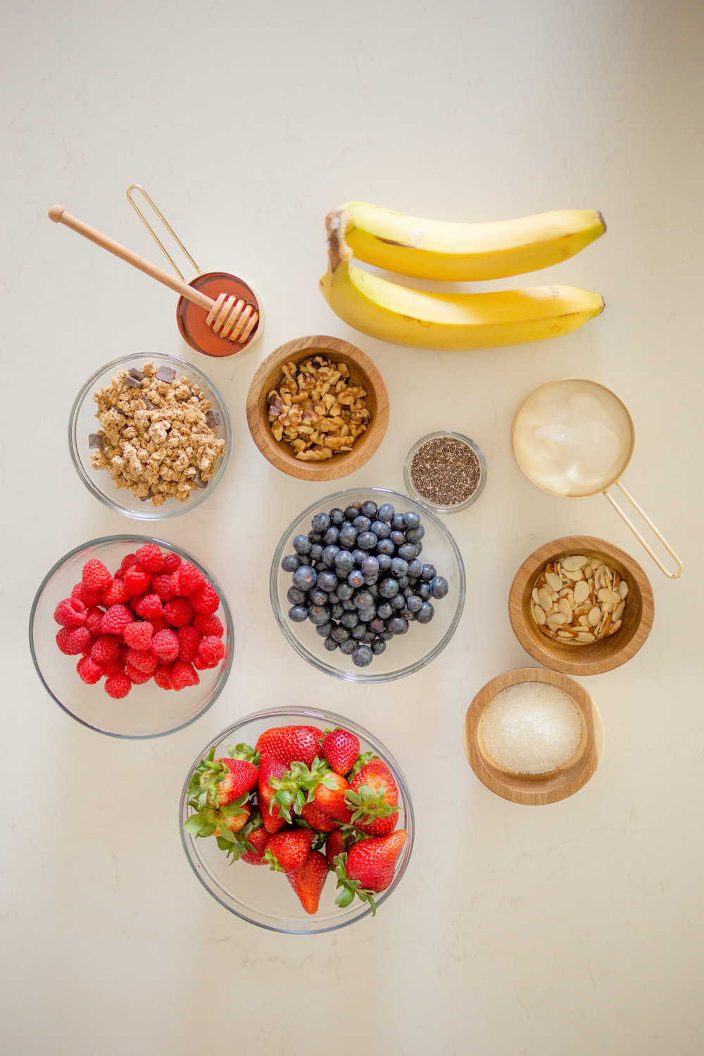 Flat lay of ingredients used for a healthy breakfast banana split: bananas, nuts, granola, raspberries, blueberries, honey, chia seeds, coconut yogurt