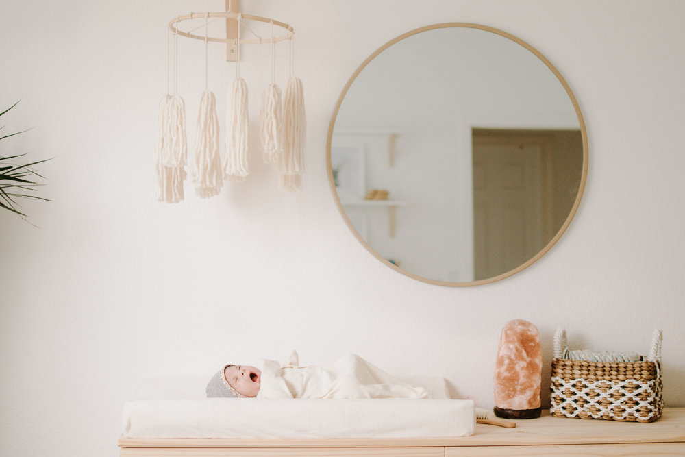 newborn on changing mat beneath a DIY boho tassel mobile for gender neutral minimalist nursery