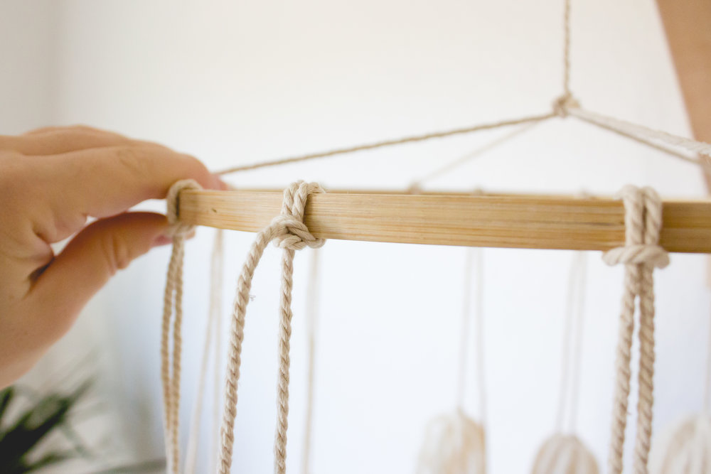 finishing touches to a DIY boho tassel mobile for gender neutral minimalist nursery
