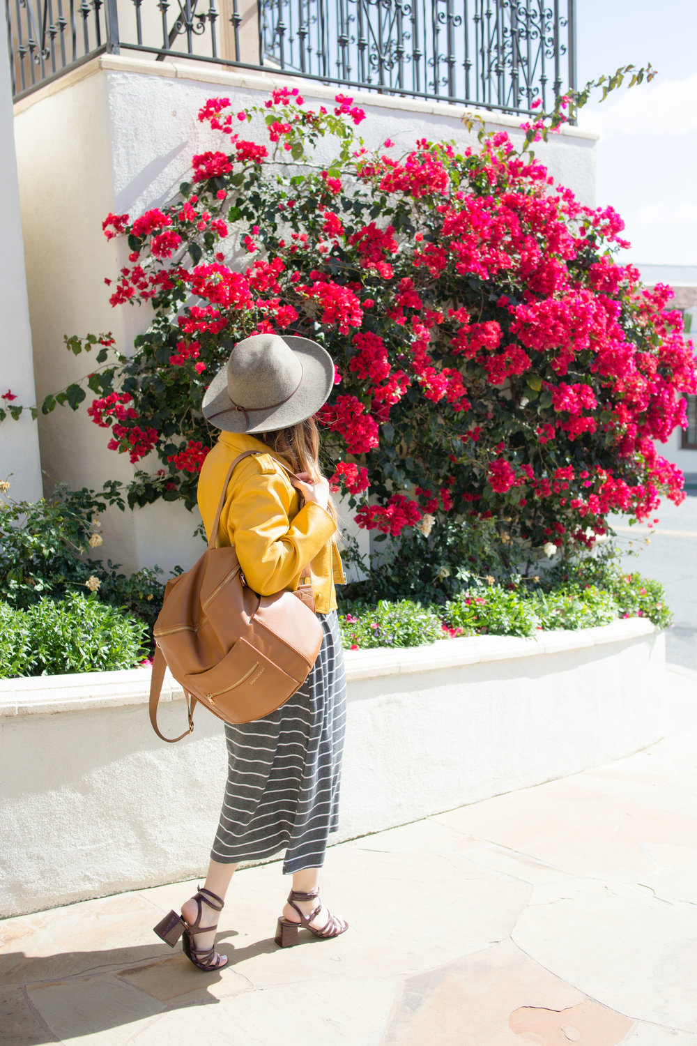 of a millenial mama wearing yellow Zara motto jacket, dwell & slumber dress, brixton hat, and fawn design backpack