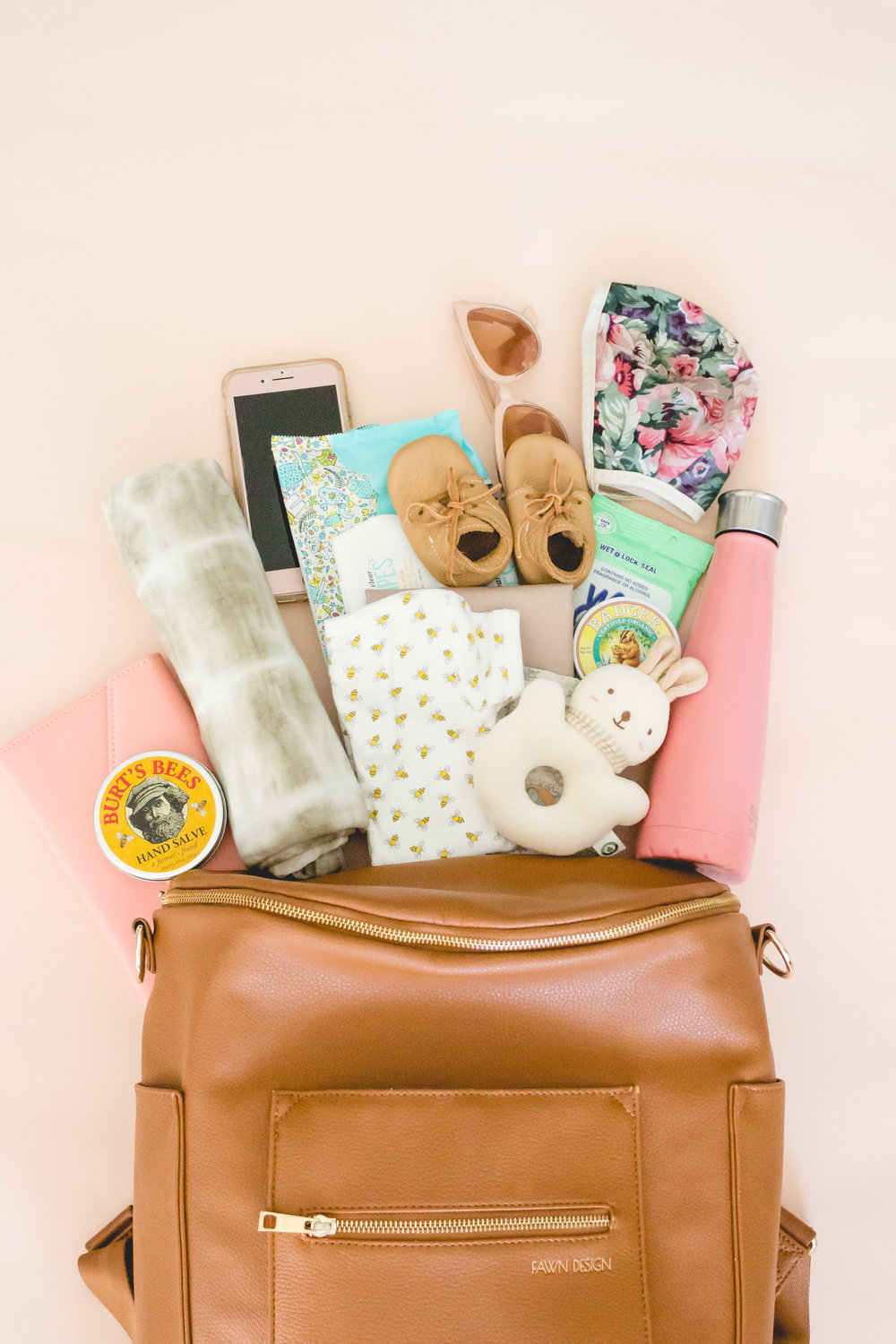 Flat Lay of Fawn Design Diaper Bag with Newborn Essentials