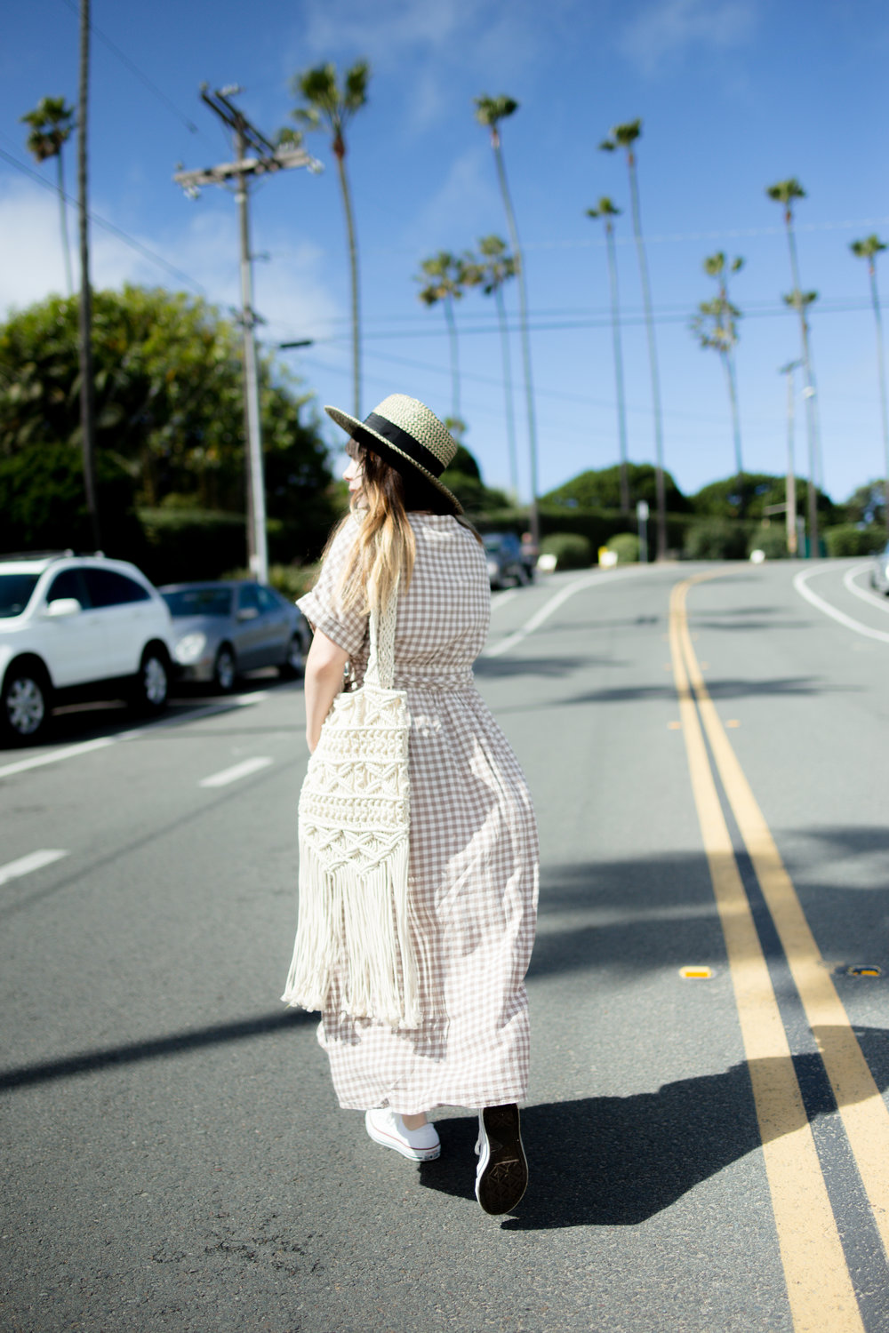 Streetstyle of Girl Wearing UO Gabrielle Linen Midi Wrap Dress and white converse chuck Taylors