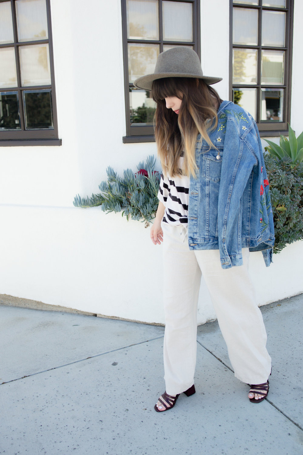Girl standing infant of white wall wearing striped linen top, embroidered H&M denim jacket and UO Structured Brim Felt Panama Hat