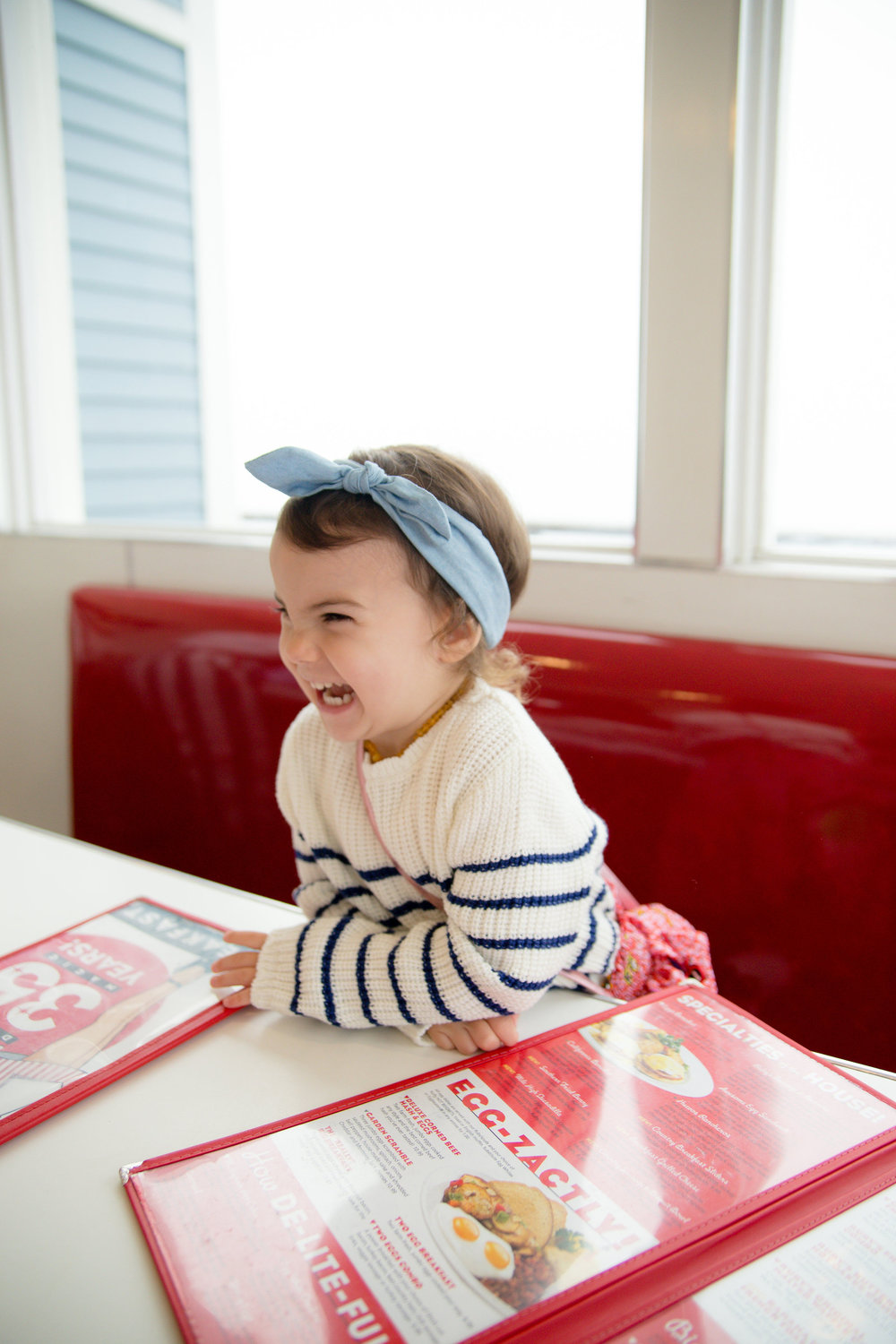 Toddler girl laughing in classic diner in Oceanside California at Ruby's at the pier