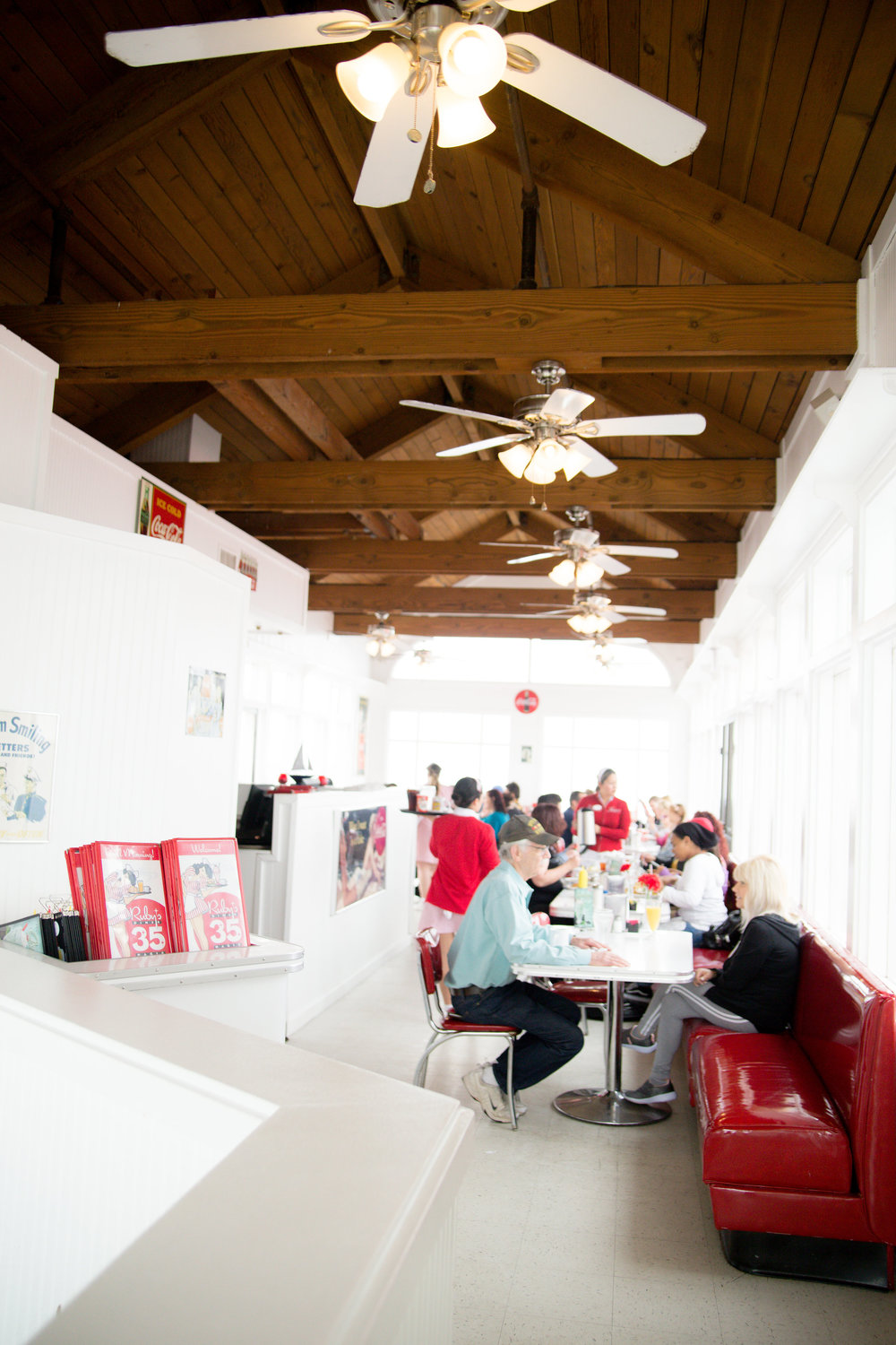 White and red classic diner interior with wood beam ceilings at ruby's on the pier in Oceanside California