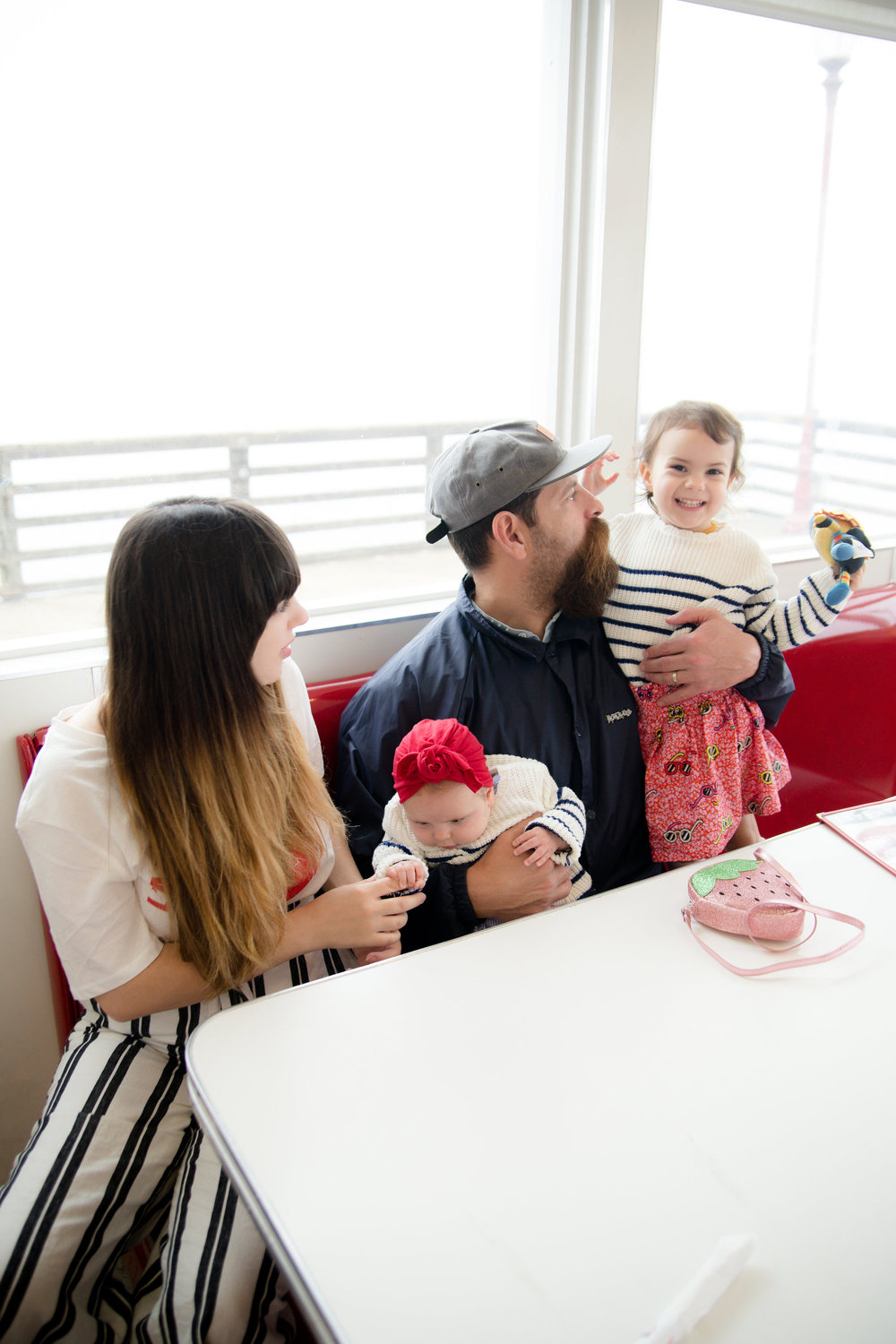 Young family laughing and smiling in classic diner rubys on the pier in oceanside California