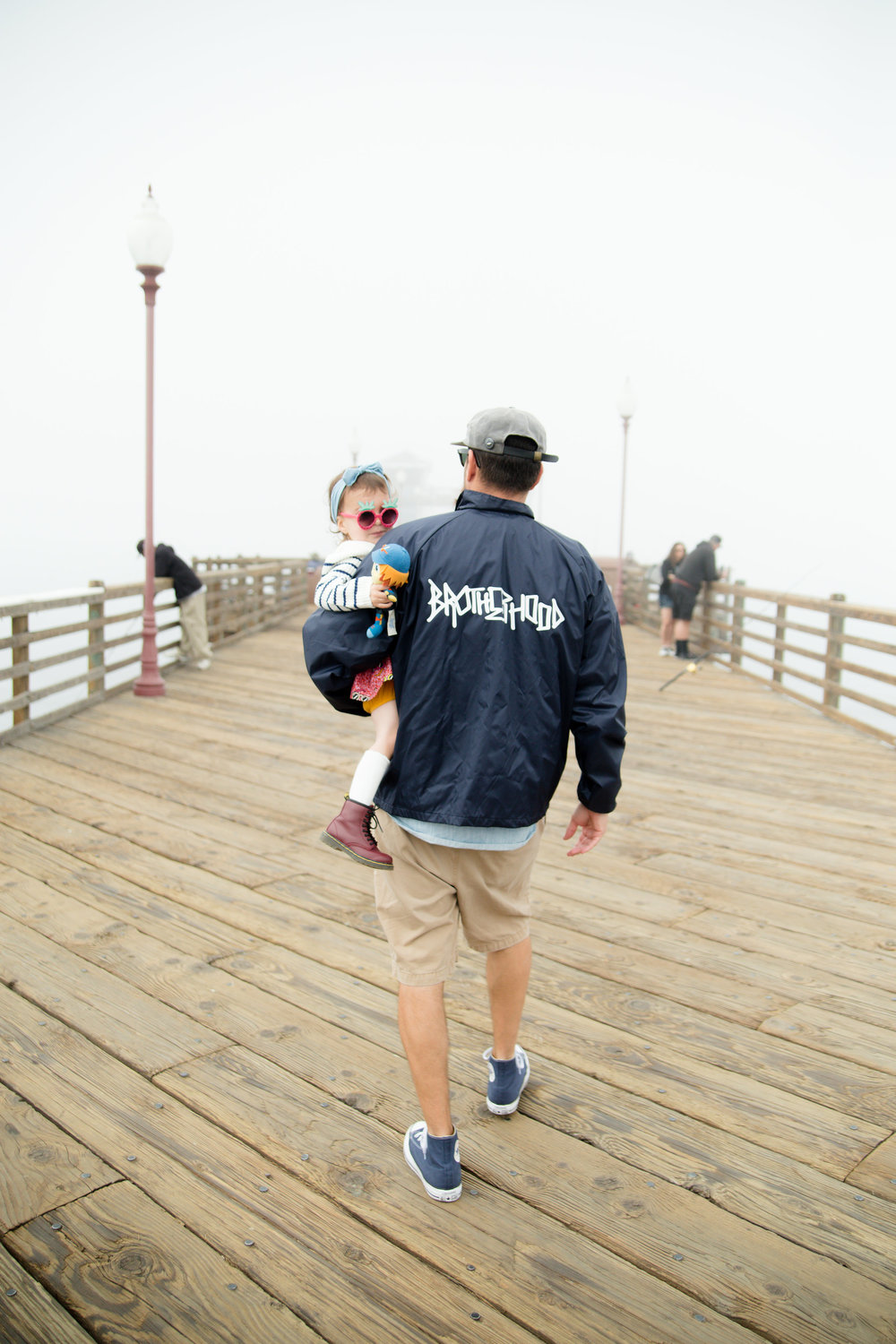 Dad wearing brotherhood walking with his stylish toddler daughter down the foggy pier in oceanside California