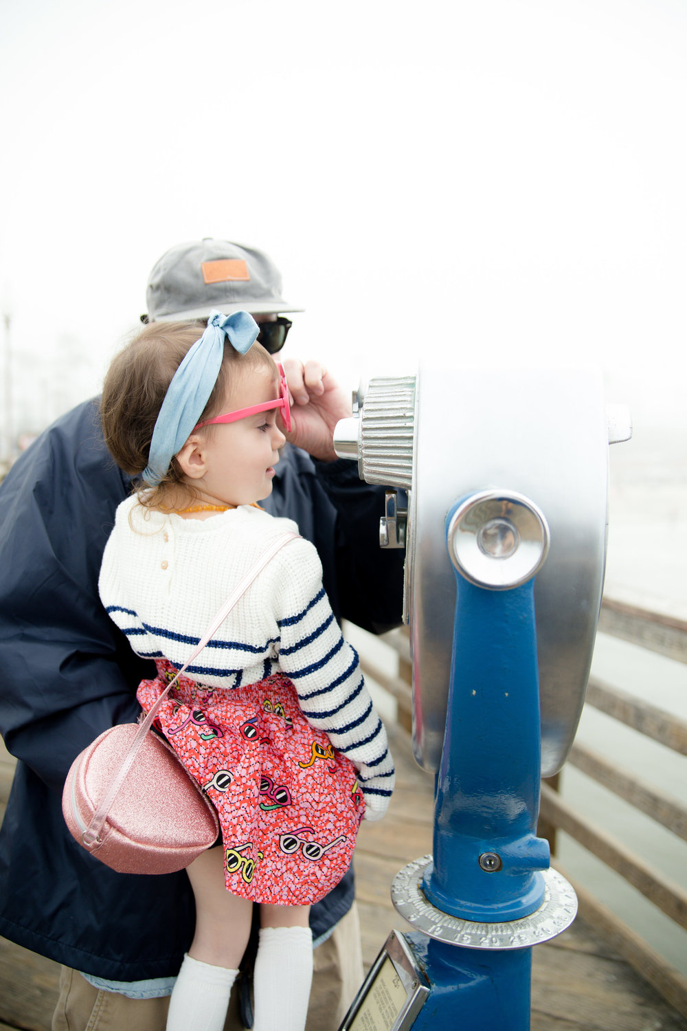 Dad lifting toddler daughter's sunglasses so she can see through the binoculars at the pier in Oceanside California