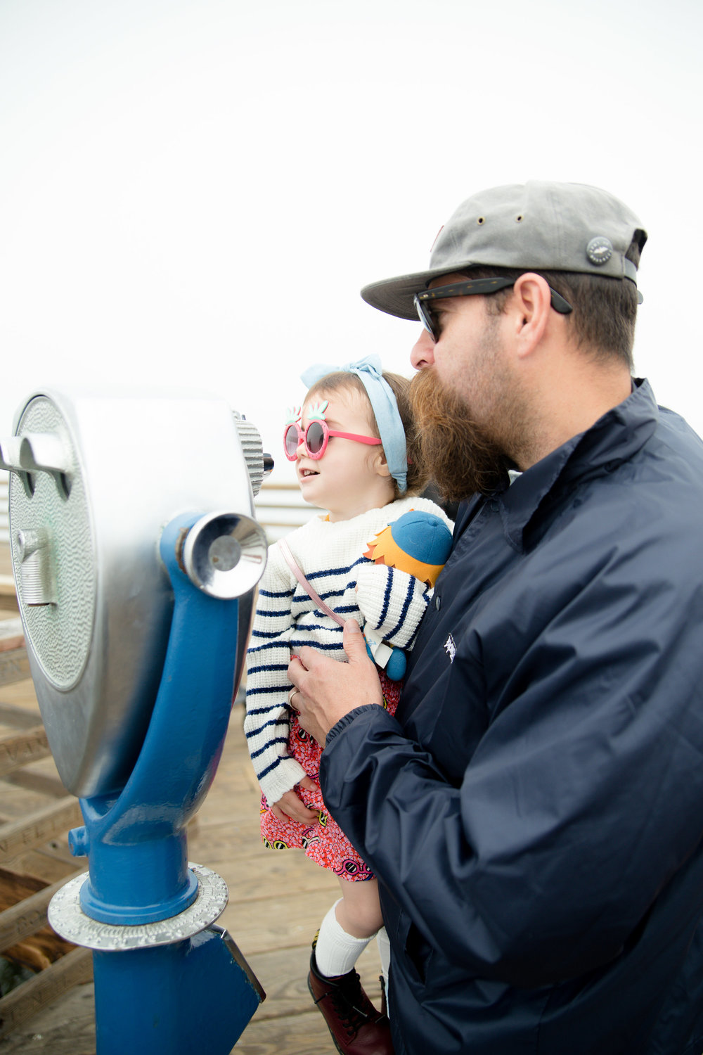 Dad lifting toddler daughter so she can see through the binoculars at the pier in Oceanside California