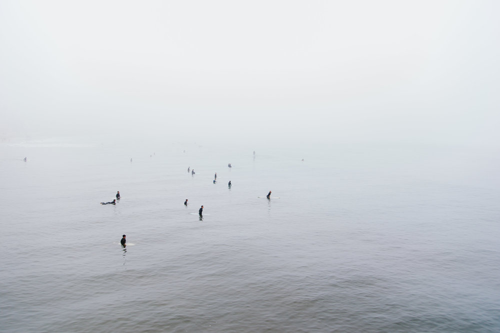 Foggy capture of surfer's in the lineup, taken from the pier in oceanside California