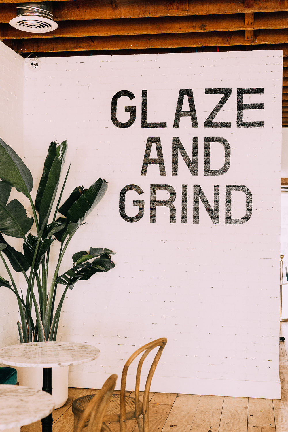 "Modern bakery interior ""Glaze & Grind"" quote wall at The Goods in Carlsbad village"