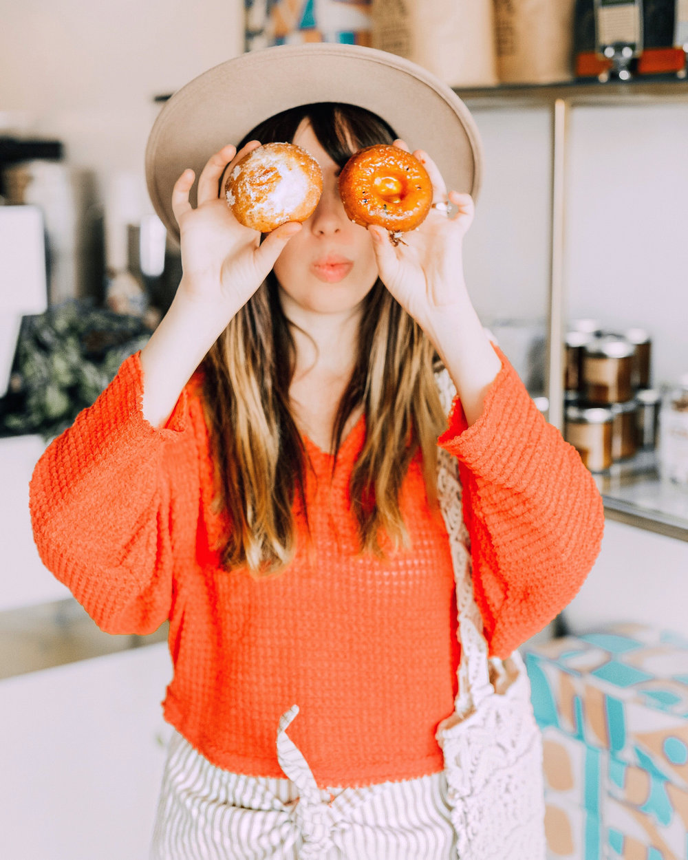 Girl wearing Brixton fedora holding gourmet donuts over her eyes at The Goods in Carlsbad Village