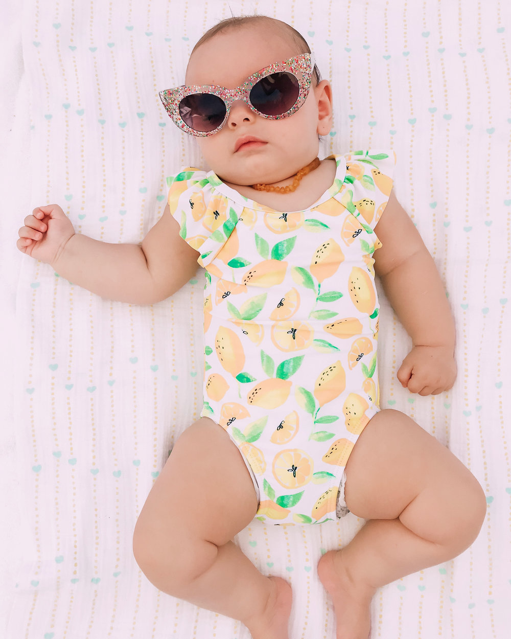 Adorable sleeping baby wearing retro sunglasses and a lemon swimsuit
