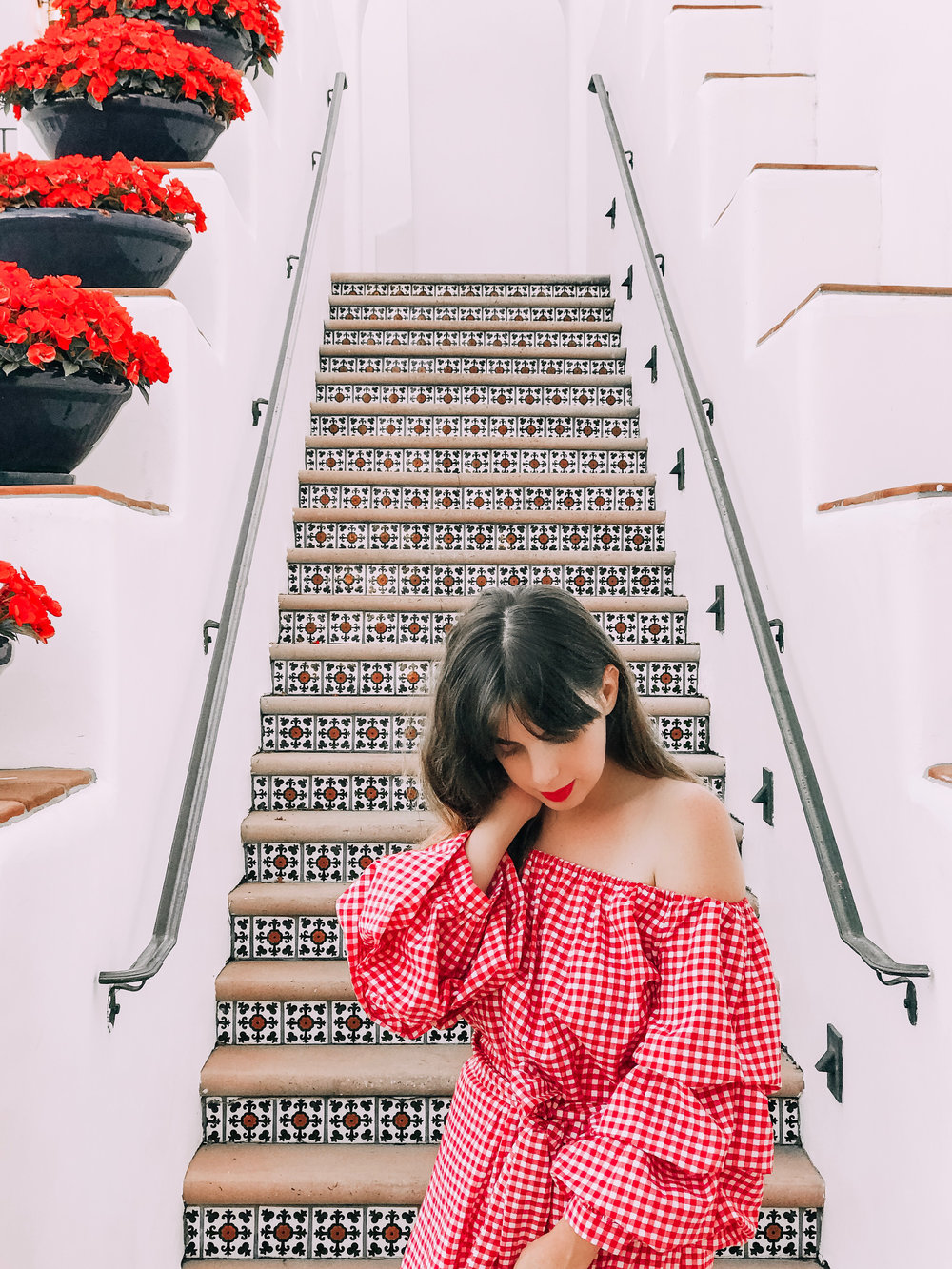 Girl wearing Ginham Bardot dress walking down Spanish tiled stairs at the Omni La Costa