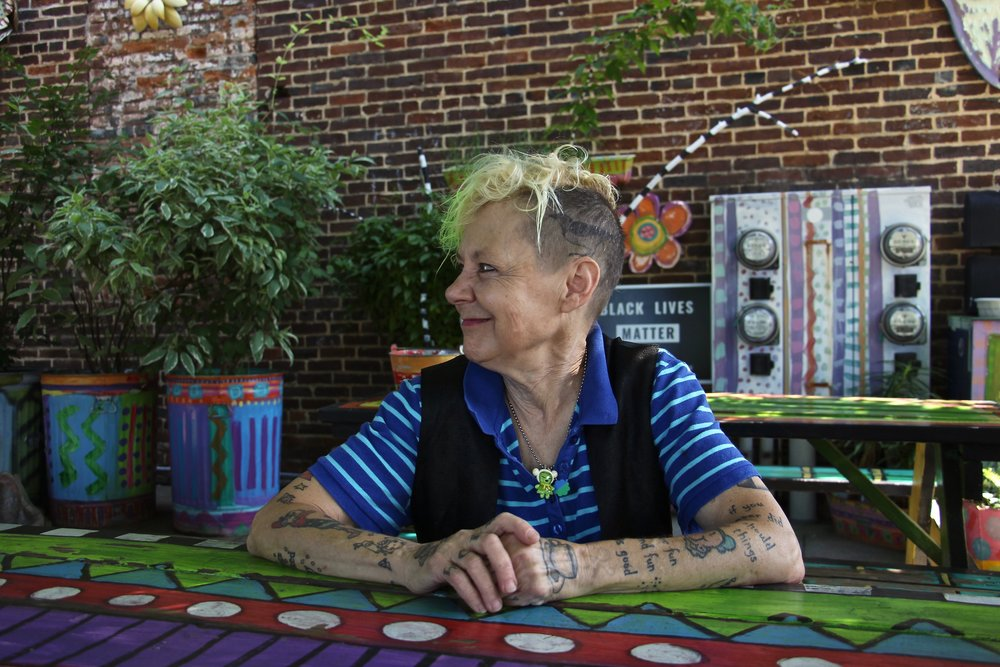"Pat Gerhard, owner of Third Street Stuff, sees dress and adornment as a form of expression and communication.  ""I like to communicate a little bit of entertainment...a bit of a visual stretch.""  Gerhard has three birds tattooed on her head ""for entertainment value."""
