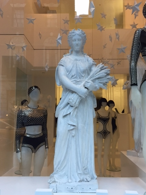 Demeter/Ceres Virgo archetype holding grain in Norma Kamali window, W. 56th St., NYC