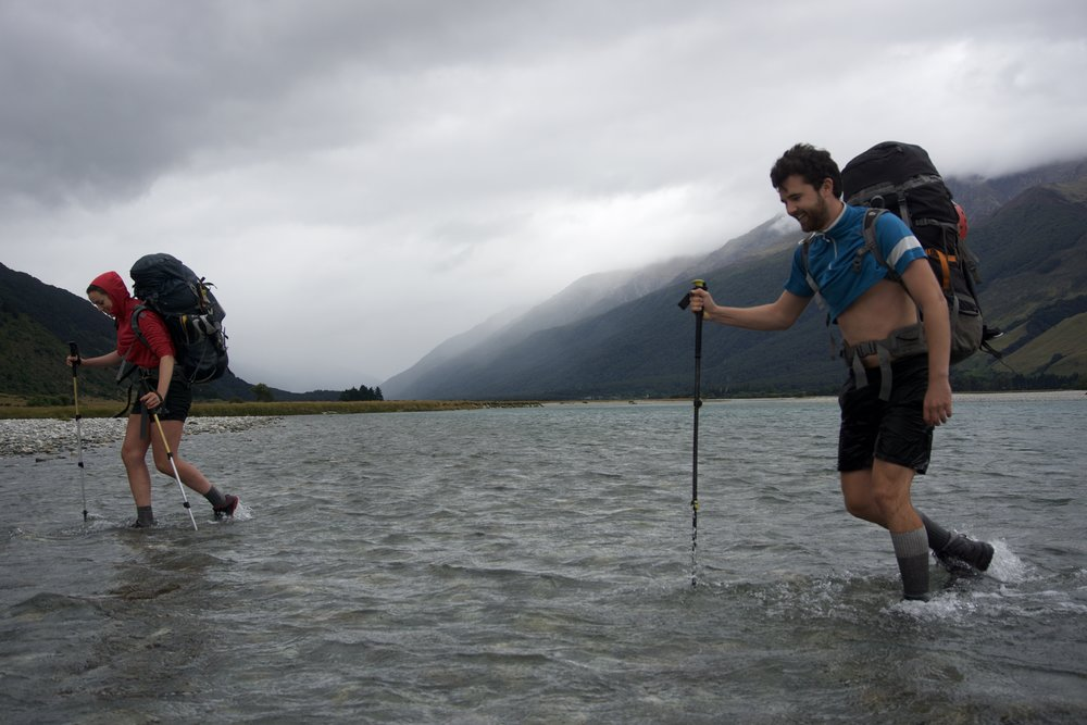 Cade and Lydia setting out across the Makarora river under ominous skies.