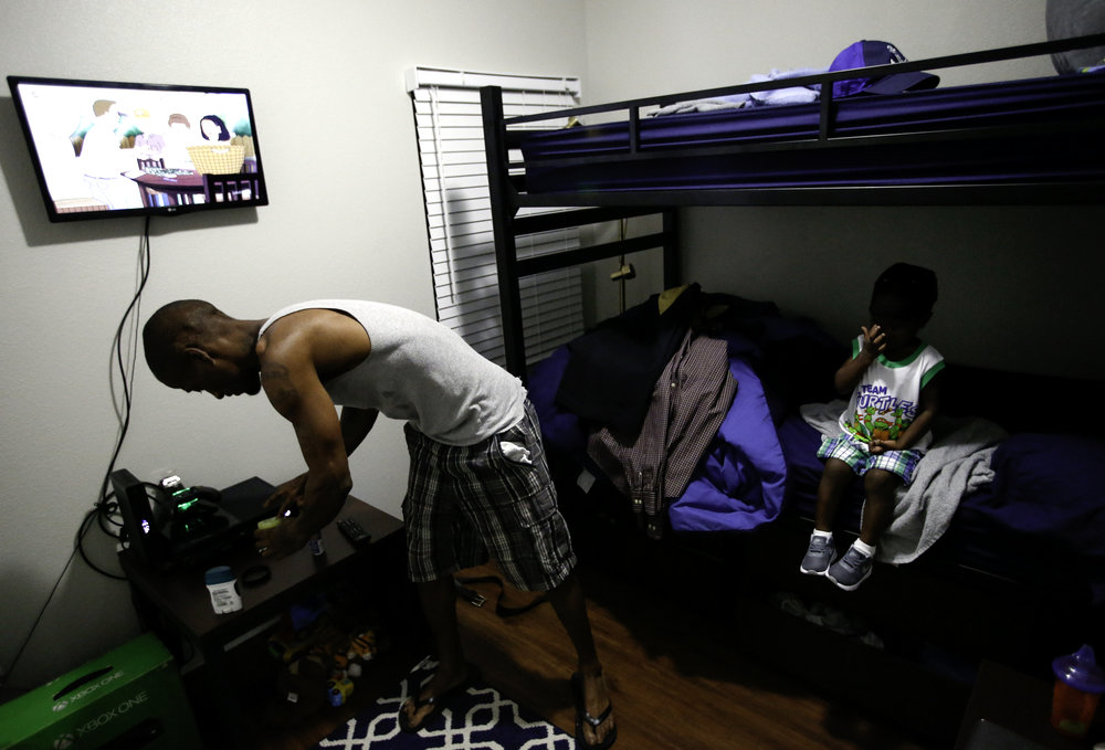 Joshua Miller and his two-year-old son Jordan get ready for the day in their room at the Family First Men's Shelter in Dallas on Monday, July 03, 2017. After weeks of bringing his son along with him for various appointments across the city, Miller prepares his son for his first day of daycare. (Tailyr Irvine/The Dallas Morning News)
