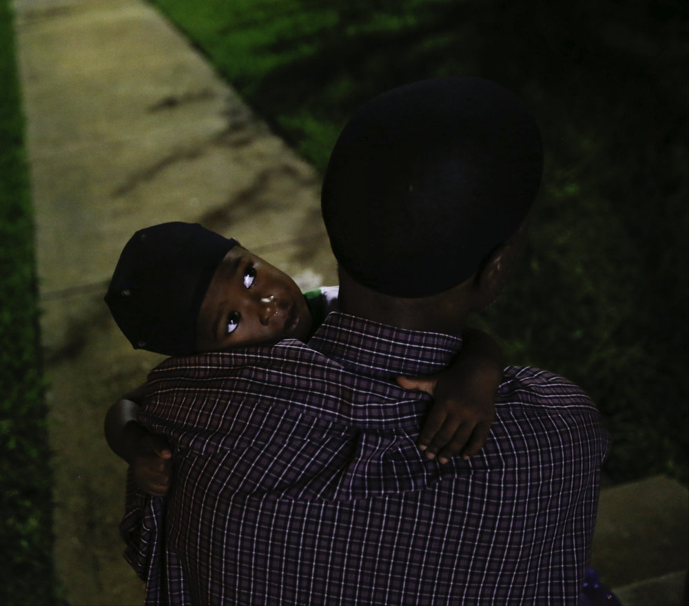 Jordan Miller, 2, sits on his fathers lap while they wait outside of Family First Men's Shelter for a van to pick him up for his first day of daycare on Monday, July 03, 2017. (Tailyr Irvine/The Dallas Morning News)