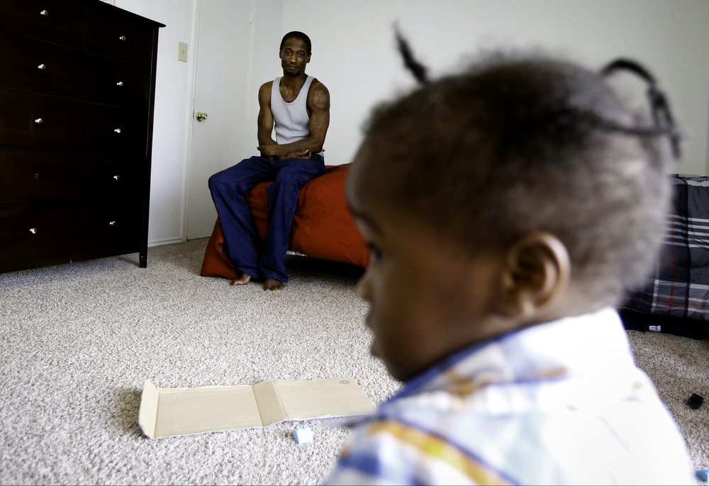 Joshua Miller watches his son, Jordan, play in their new apartment in Dallas on Saturday, July 22, 2017. After weeks of living in a room at Family First Men's Shelter, Miller moved to a transitional apartment where he can stay for up to 18 months. Miller's temporary job at Goodwill turned into a permanent position and he said thankful for the support he received from the shelter. (Tailyr Irvine/The Dallas Morning News)