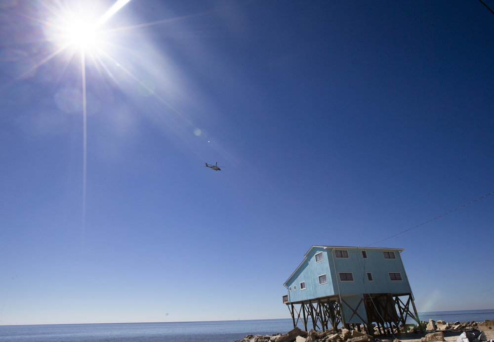 A Coast Guard helicopter flies over Alligator Drive in Alligator Point on October 12, 2018. A large portion of Alligator Drive was destroyed by Hurricane Michael leaving residents unable to drive to their homes.